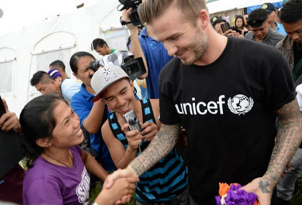 Beckham (right) greets survivors of Typhoon Haiyan during a visit to a tent city in Tacloban city. AFPpic