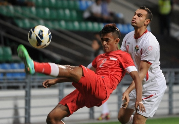 Jordanian forward Thaer Bawab (right) and Singapore's Muhammad Shakir fight for the ball during the match. AFPpic