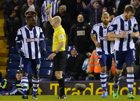 Victor Anichebe (left) is given a yellow card after taking off his shirt after scoring against Chelsea/AFP pic.