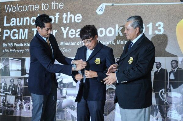 Khairy Jamaluddin helping Nicholas Fung (centre) with his PGM jacket, witnessed by Tun Ahmad Sarji bin Abdul Hamid.
