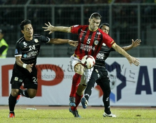 Milorad Janjus (center) of Sarawak is challenged by Perak's Mohamad Hisyamudin Mohamad Shaari in a Super League match yesterday. Sarawak won 1-0 with Janus hitting the winner from a freekick. Picture by AZAM MUHAMAD SUBRI/asiana.my